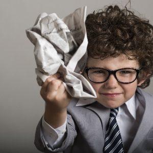 新聞を丸める男の子